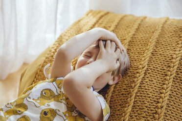 Little boy lying on cushion covering face with his hands - MFF03633