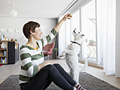 Woman sitting on the floor in the living room with her dog - RBF05670