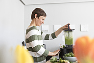 Smiling woman preparing green smoothie in the kitchen - RBF05679