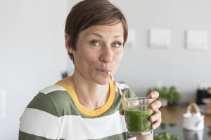 Portrait of woman drinking green smoothie in the kitchen - RBF05682