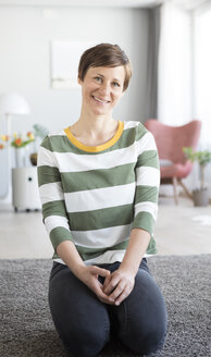 Portrait of smiling woman sitting on the floor in the living room - RBF05694