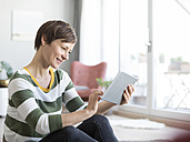 Portrait of smiling woman sitting on the floor in the living room using tablet - RBF05697