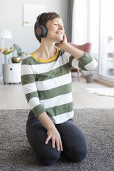 Portrait of smiling woman sitting on the floor in the living room listening music with headphones - RBF05700