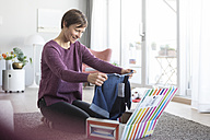 Smiling woman at home unpacking parcel with garment - RBF05709