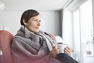 Portrait of woman relaxing with cup of coffee at home - RBF05721