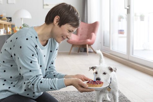 Smiling woman presenting her dog a birthday cake - RBF05727