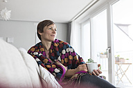 Portrait of woman relaxing with cup of coffee at home - RBF05730
