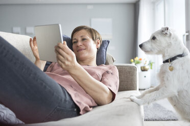 Portrait of smiling woman lying on the couch using tablet while dog watching her - RBF05739