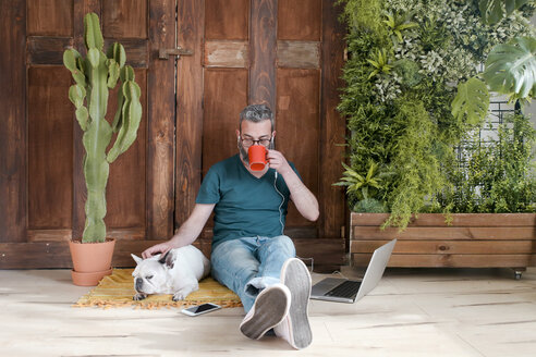Bearded man sitting with his dog on the floor at home drinking coffee - RTBF00897