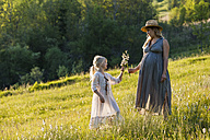 Pregnant mother and daughter on a meadow - TCF05430