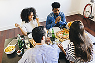Group of friends having a pizza at home - GIOF02737