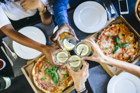 Group of friends having pizza and clinking glasses of water at home - GIOF02740