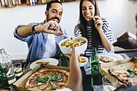 Happy friends having French fries and pizza at home - GIOF02752