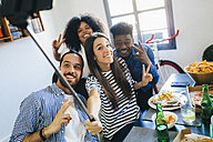 Group of friends posing for a selfie at dining table at home - GIOF02755