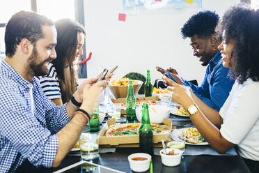 Friends using cell phones at dining table - GIOF02758
