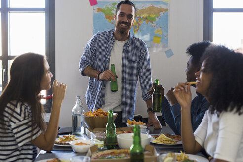 Group of friends socializing with beer and fast food at home - GIOF02770