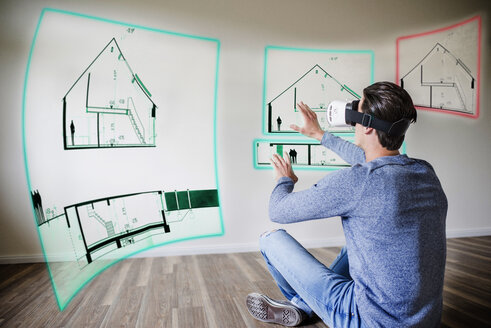 Man in apartment wearing VR glasses exploring house - UUF10810