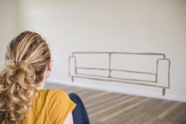 Young woman in new home sitting on floor thinking about interior design - UUF10813