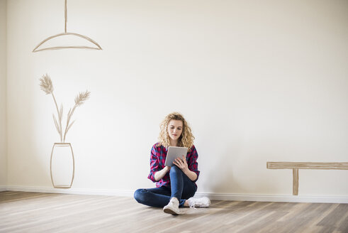 Young woman in new home sitting on floor using tablet - UUF10816