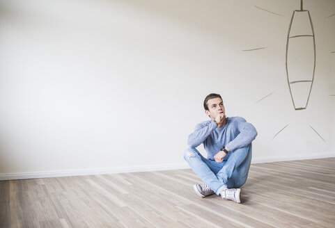 Young man in new home sitting on floor thinking about interior decoration - UUF10819