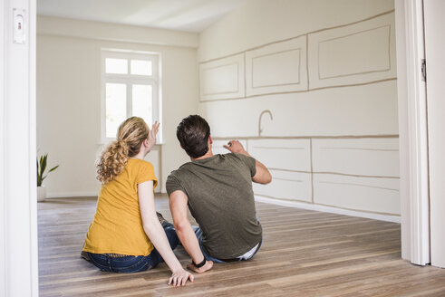 Young couple in new home sitting on floor thinking about interior design - UUF10822