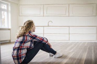 Young woman in new home sitting on floor thinking about interior design - UUF10825