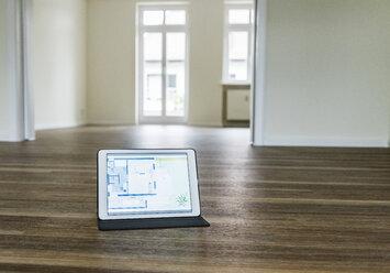 Tablet with floor plan on wooden floor - UUF10828