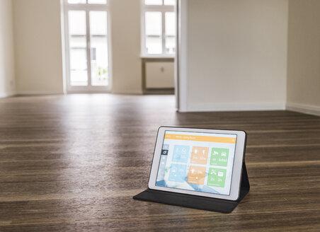 Tablet with smart home apps on wooden floor - UUF10831