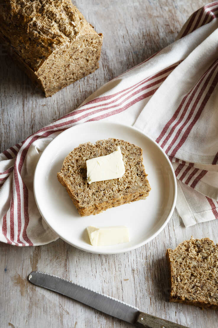 Home.baked spelt bread with flax and sesame, slice with butter - EVGF03228 - Eva Gruendemann/Westend61