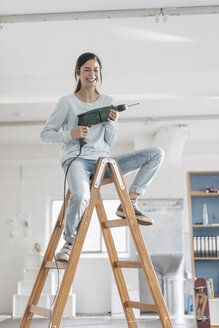 Young woman in her new flat sitting on ladder, holding electric drill - JOSF01086