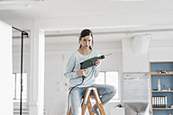Young woman in her new flat sitting on ladder, holding electric drill - JOSF01107