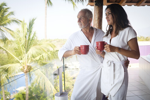 Young woman and older man drinking coffee in bathrobes on balcony - ABAF02156