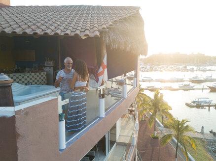 Unequal couple - older man and young woman enjoying evening on penthouse terrace, Nuevo Vallarta, Nayarit, Mexico - ABAF02162