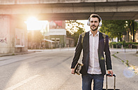 Young man on the move with skateboard, rolling suitcase and headphones - UUF10836