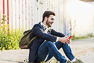 Smiling young man sitting on pavement checking cell phone - UUF10842