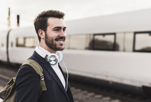 Smiling young man on platform as train coming in - UUF10854