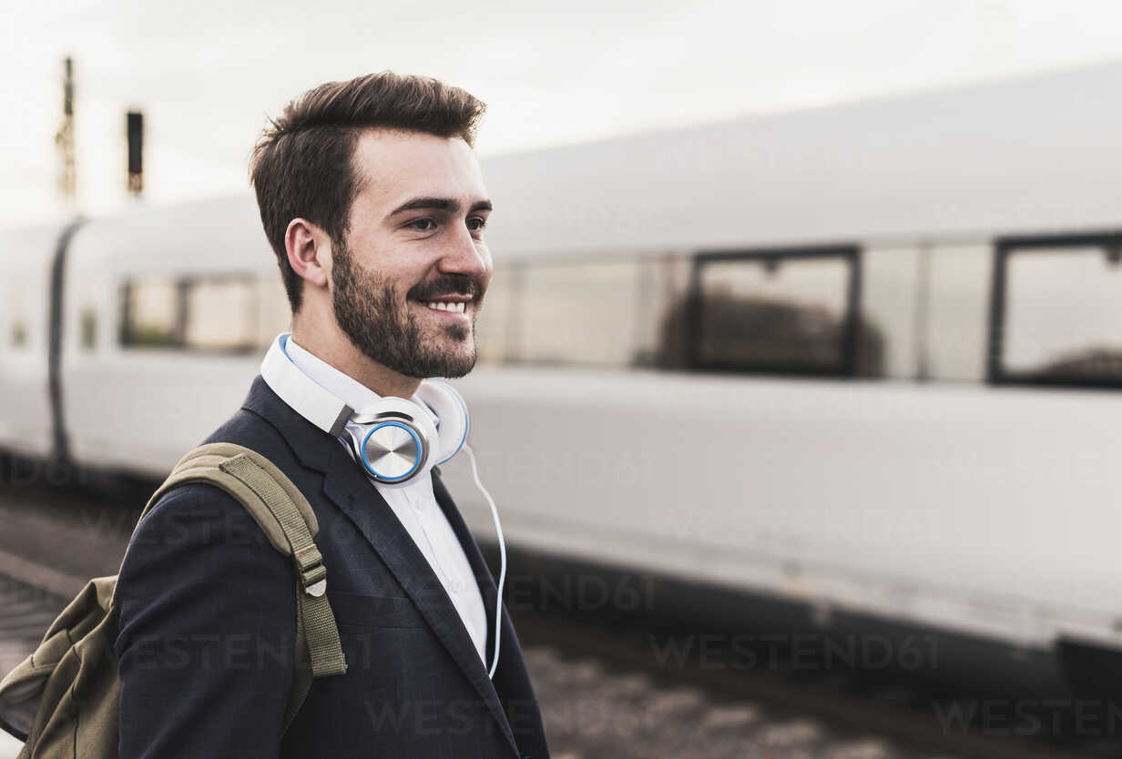 Smiling young man on platform as train coming in - UUF10854 - Uwe Umstätter/Westend61