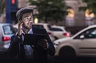 Young man in the city with earphones and tablet - UUF10857