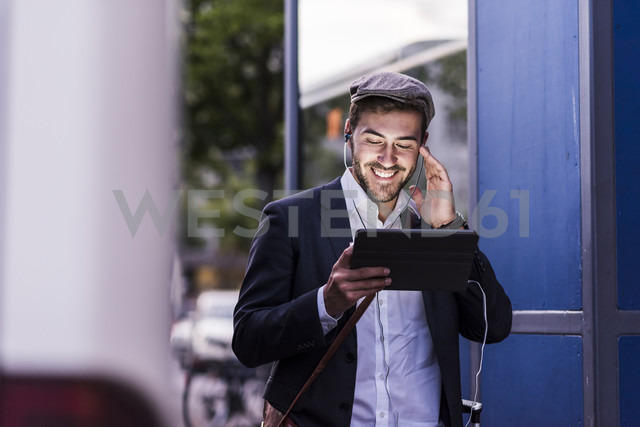 Smiling young man in the city with earphones and tablet - UUF10860 - Uwe Umstätter/Westend61