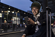 Young man in the city with headphones and cell phone in the evening - UUF10863