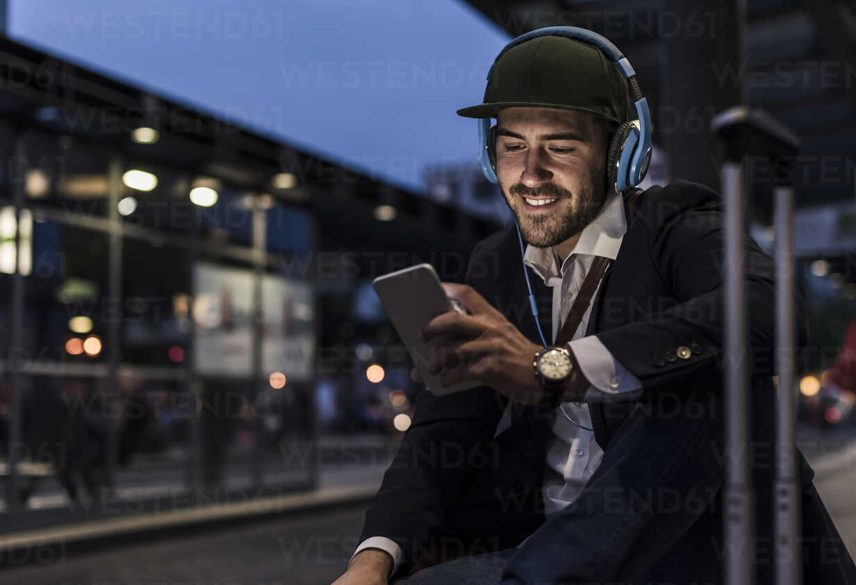 Young man in the city with headphones and cell phone in the evening - UUF10863 - Uwe Umstätter/Westend61