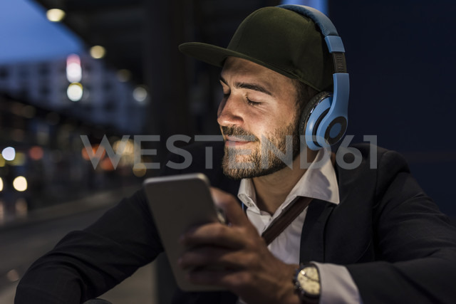 Young man in the city with headphones and cell phone in the evening - UUF10866 - Uwe Umstätter/Westend61