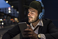 Young man in the city with headphones and cell phone in the evening - UUF10866