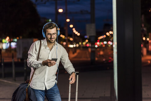 Young man in the city with headphones and cell phone at night - UUF10869