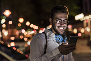 Smiling young man in the city checking cell phone at night - UUF10872