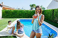 Woman holding drink at the poolside with friends in background - KIJF01512