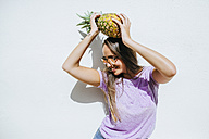 Happy young woman holding pineapple in front of white wall - KIJF01515