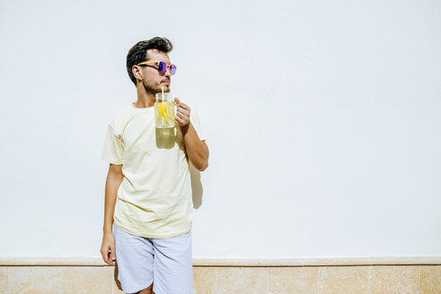 Man with sunglasses and lemonade in front white wall - KIJF01518