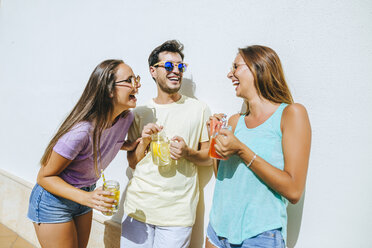 Laughing friends holding refreshing drinks in front of white wall - KIJF01521