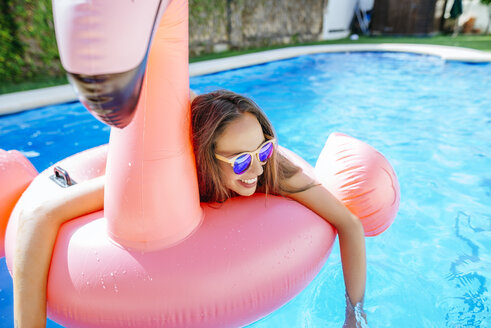 Happy young woman with pink flamingo float in swimming pool - KIJF01524